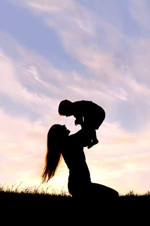A silhouette of a happy young mother, laughing as she plays with her toddler child and lifts him over her head outside at sunset. photo