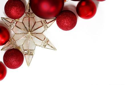 estrella de la vida: Decoraciones bombilla roja brillantes de Navidad y una estrella adorno del árbol de oro están en la esquina que enmarca un fondo blanco para el texto, copyspace Foto de archivo