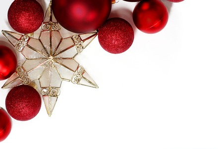 christmas light bulbs: Red sparkly Christmas Bulb Decorations and a gold tree topper star are in the corner framing a white background for text, copyspace Stock Photo