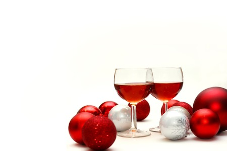 recieve: Two wine glasses filled with red wine sit on an isolated white background in surrounded by silver and red sparkling Christmas Bulb Decorations