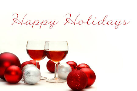 recieve: Two wine glasses filled with red wine sit on an isolated white background with Happy Holidays Text, surrounded by silver and red sparkling Christmas Bulb Decorations Stock Photo