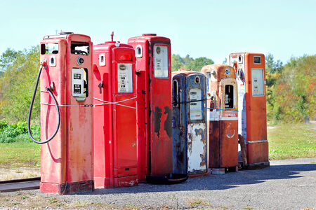 abandoned gas station: A row of old, colorful, vintage abandoned gas tanked at a fill up station in the country.