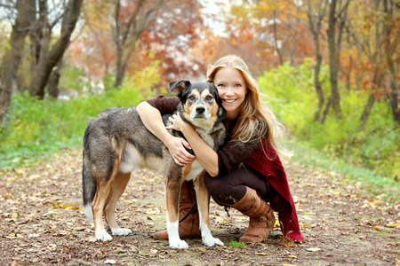 A thirty year old woman is stopping to hug her German Shepherd dog as they are walking through the fallen leaves in the woods on an Autumn day.
