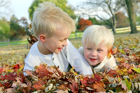 Two young children, a little boy and his baby brother are playing outside and jumping in a pile of fallen colorful leaves on an Autumn day. photo