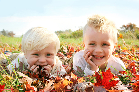 two year old: A portrait of two, happy, smiling young children, playing outside in a pile of red and yellow fallen Maple Tree leaves on an Autumn day. Stock Photo