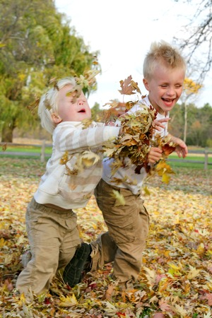 Two young boy children are playing outside on an autumn day, chasing eachother and throwing yellow fall leaves.