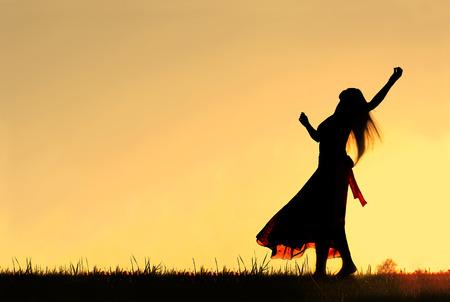 長いブロンドの髪の長いスカートをはいている女性はダンス、紡績、夕方の空に対してシルエットながら 写真素材