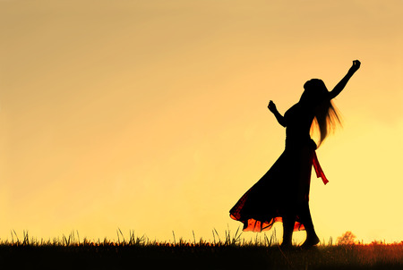 A woman wearing a long skirt, with long blonde hair, is dancing and spinning, while silhouetted against the evening sky Stockfoto