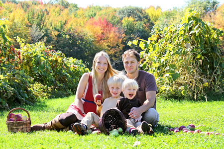 people and nature: a happy family of four attractive caucasian people is sitting in an apple orchard in the Autumn forest, eating a fresh fruit picnic