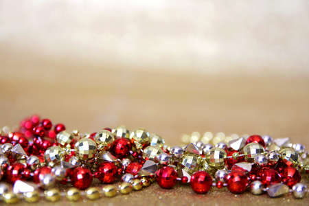 A collection of red and gold Marti-Gras beaded necklaces frame the bottom of a  gold glitter fabric. photo