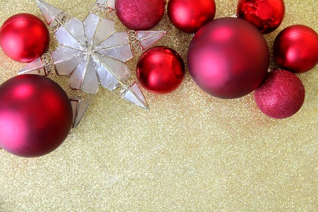 red christmas bulb decorations and a star shaped tree topper border the top of a gold