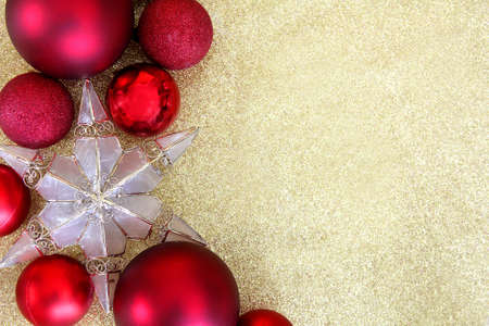 Red Christmas bulb decorations and a star shaped tree topper border the edge of a  gold glitter fabric with copy-space.