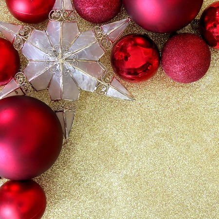 red christmas bulb decorations and a star shaped tree ornament border the corner of a gold