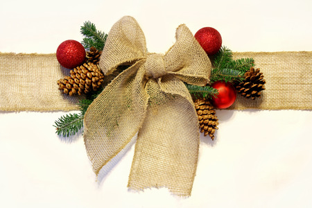 A tan colored burlap ribbon is tied into a bow as if wrapped around a Christmas present, surrounded by natural pinecones, spruce branches and holiday ornaments, and isolated on a white background.