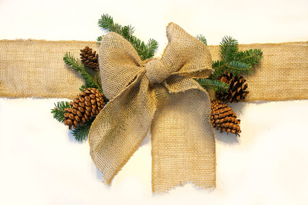 A burlap fabric ribbon is isolated on a white background, surrounded by pine cones and evergreen Christmas tree branches. Stock Photo