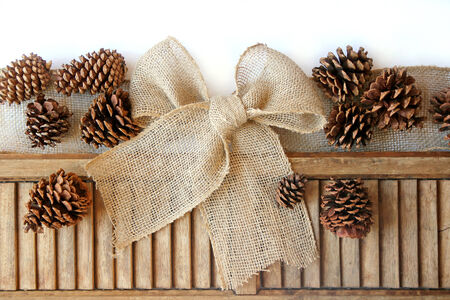 A burlap Ribbon is tied into a Christmas Gift bow next to vintage wooden shutters and natural pinecones, isolated on a white background.