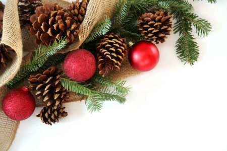 christmas bulbs: Red Christmas Tree ornaments, pinecones, evergreen branches, and burlap fabric are creating a frame, isolated on a blank white background.