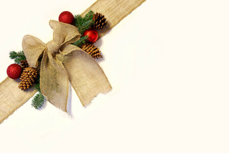 A tan colored burlap ribbon is tied into a bow in the corner as if wrapped around a Christmas present, surrounded by natural pinecones, spruce branches and holiday ornaments, and isolated on a white background.