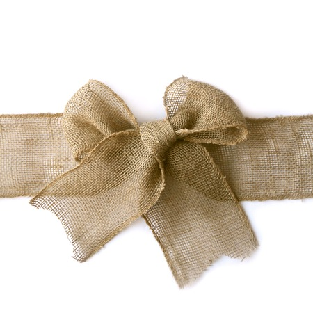 sackcloth: A natural colored burlap wribbon is tied in a bow as if wrapped around a Christmas present, isolated on a white background, with vertical copyspace