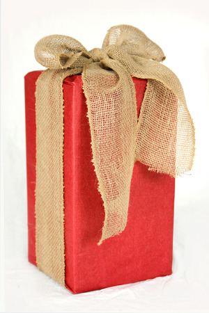 a big rectangular shaped christmas gift box is wrapped in red paper and a burlap ribbon