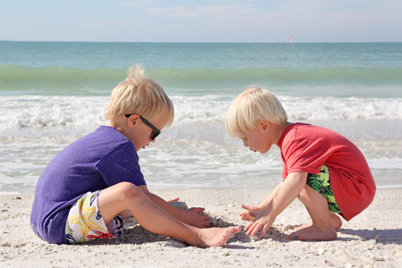 sandcastle: Two young boy children are sitting on the white sand beach, digging a hole with their hands to build a sandcastle, next to the ocean while in summer vacation. Stock Photo