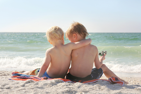 2 year old: Two young children, a boy and his little brother, are sitting in the white sand at the beach by the ocean, with their arms around each other, and their backs to the camera.