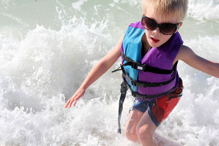 A young child is swimming and playing in the ocean waves at the beach, while wearing sunglasses and a life jacket.