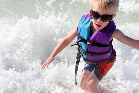Ein kleines Kind wird schwimmen und spielen in den Wellen des Ozeans am Strand, während trägt eine Sonnenbrille und eine Schwimmweste.