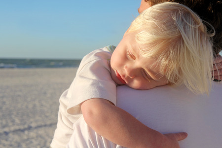2 year old: A young child is sleeping in his fathers safe and protective embrace while on a walk on the white sand beach by the ocean at sunset.