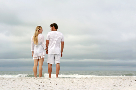 thirty: A happy young married couple is holding hands and looking at each other as the stand on a white sand beach looking out over the ocean while on vacation.