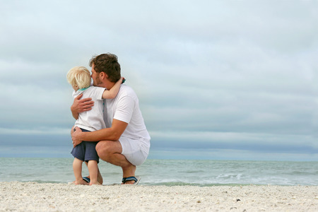 A father and his young toddler son are hugging as they stand on a white sand beach and look out over the ocean while on vacation. 免版税图像