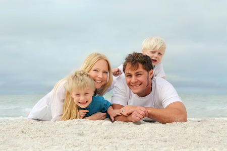 A portrait of a happy family of four, young, attractive caucasian people, including mother, father, baby, and child, are relaxing on a white sand beach by the ocean on a cloudy summer day. 免版税图像