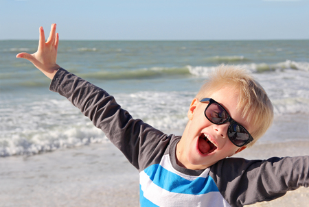 A super happy young child is smiling with joy with his arms raised up while standing on the white sand beach by the ocean on summer vacation.