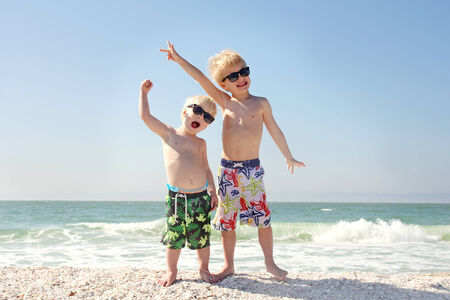 break: Two young children are happily holding their arms in the air as they stand on the beach by the ocean on a family vacation.