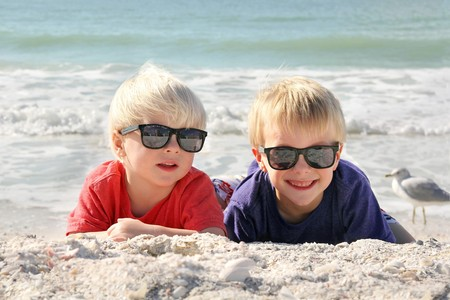 5 year old: Two happy young children, a little boy and his toddler brother, are laying on the white sand beach in the sun, wearing sunglasses on family summer vacation.