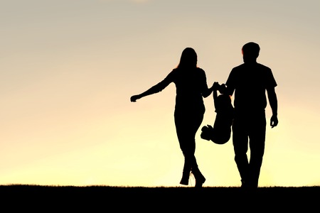 mom baby: A silhouette of a family of three people, including mother, father, and young child are playing around while walking outside at sunset.