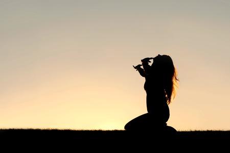 여자 공기에 그녀의 손으로 무릎을 꿇고기도하고, 감사하고, 하나님 께 항복의 실루엣.
