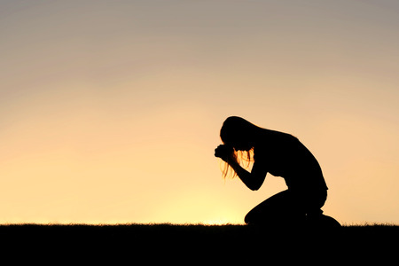 persons: A silhouette of a young Christian woman is bowing her head in prayer, and desperation outside during sunset.