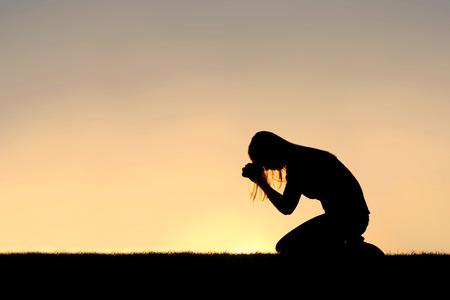 osoba: Silueta mladé křesťanské ženy se sklonila hlavu v modlitbě, a zoufalství venku při západu slunce.