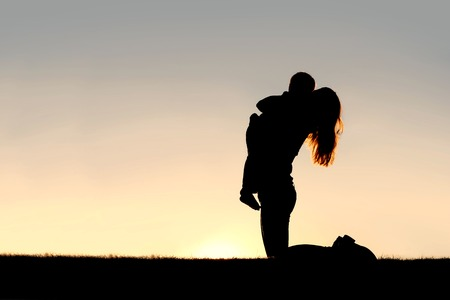 fun day: A silhouette of a happy young mother, laughing as she plays with her toddler child and gives him a big hug, isolated against the sunset.