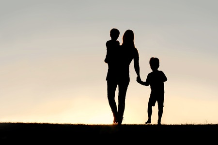 Silhouette of a young mother walking and lovingly holding hands with her happy little child, while holding his baby brother, outside in front of a sunset in the sky. Stockfoto