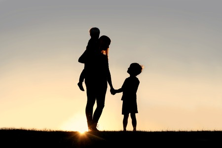 Silhouette of a young mother lovingly holding hands with her happy little child, while holding his baby brother, outside in front of a sunset in the sky. Stockfoto