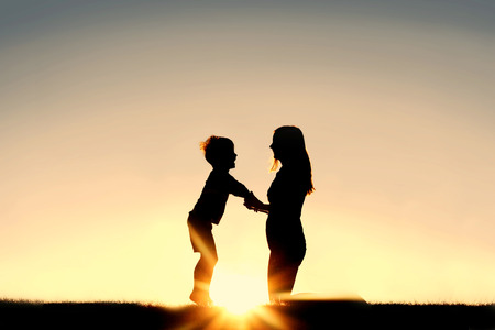 parent child: Silhouette of a young mother lovingly holding hands with her happy little child outside in front of a sunset in the sky. Stock Photo