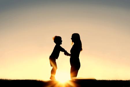 Silueta de una joven madre sosteniendo amorosamente las manos con su pequeño hijo feliz fuera en frente de una puesta de sol en el cielo. Foto de archivo - 38380655