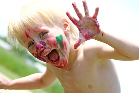 그의 얼굴이 지저분한 페인트에 덮여있는 동안 행복 한 젊은 유치원 세 아이 미소를 카메라 스톡 콘텐츠