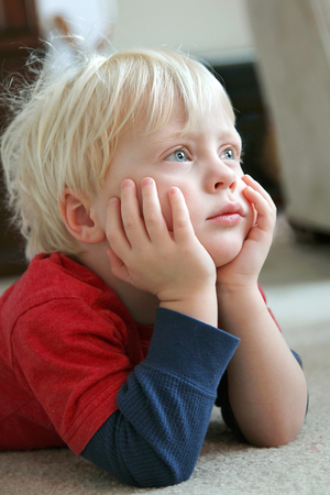 An adorable young toddler boy child is laying on his living room floor, resting his head in his hands, watching television.