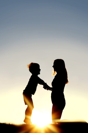 Silhouette of a young mother lovingly holding hands with her happy little child outside in front of a sunset in the sky. Archivio Fotografico