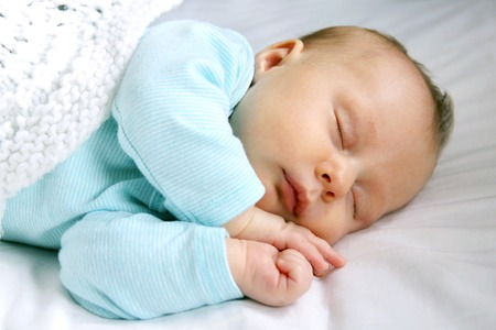A sweet newborn infant girl is sleeping peacefully while snuggled in warm white blankets