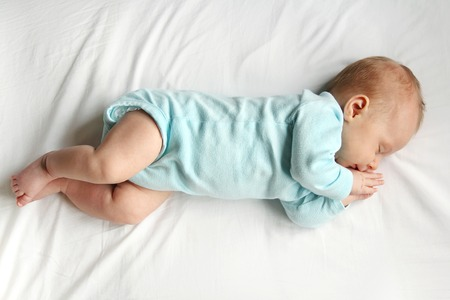 four month: A precious newborn infant is laying on a comfortable white bed, sleeping peacefully.