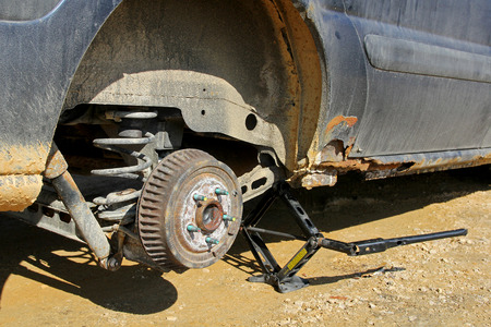 lifted: An old rusty automobile is lifted up on a jack with the wheel removed to change the tire.